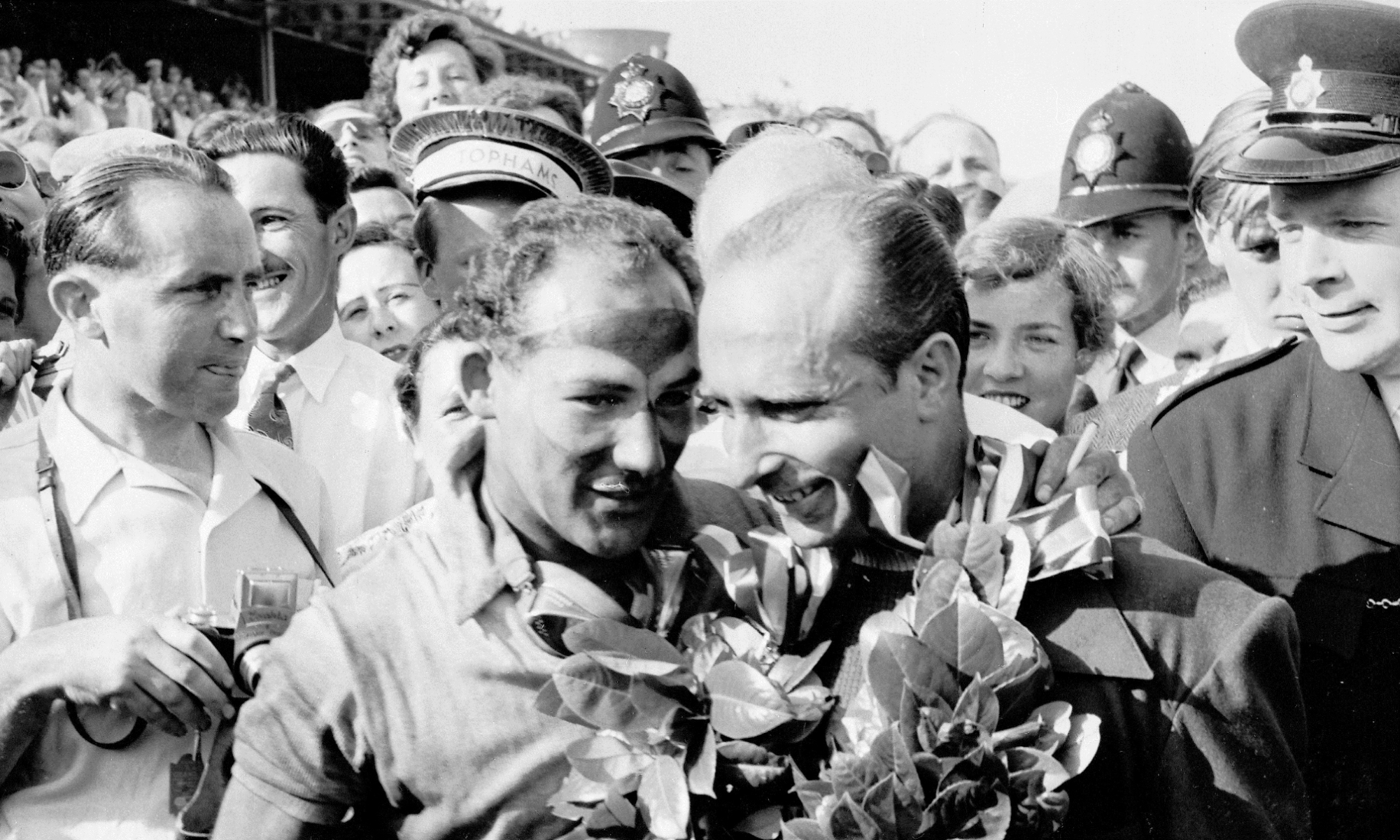1955 British Grand Prix winner Stirling Moss and runner-up Juan Manuel Fangio on the winners' podium.