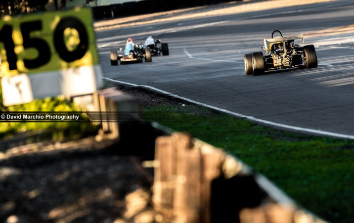 A group of Formula Libre racecars flying past the braking markers towards Cape Town corner with Sean le Riche behind the wheel of the Seleka Racing Formula Renault. Image taken during the 6th round of the Power Series held at Killarney International Raceway.