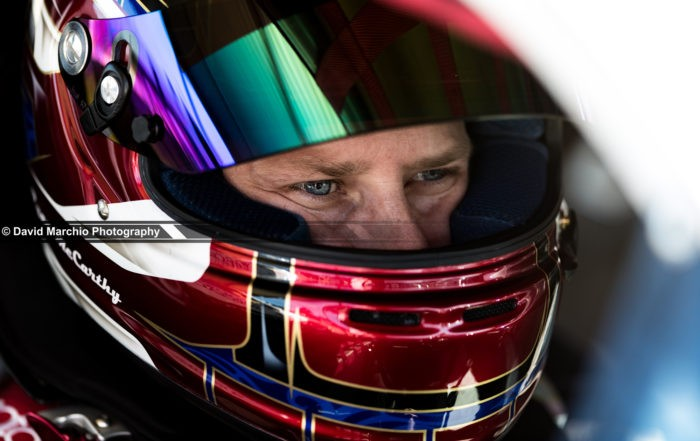 Concentration - capturing the moment of intense focus on a drivers face is tremendous, and having the narrow depth of field, leading ones eye to the focus and clarity of his eye makes this a beautiful image for me.