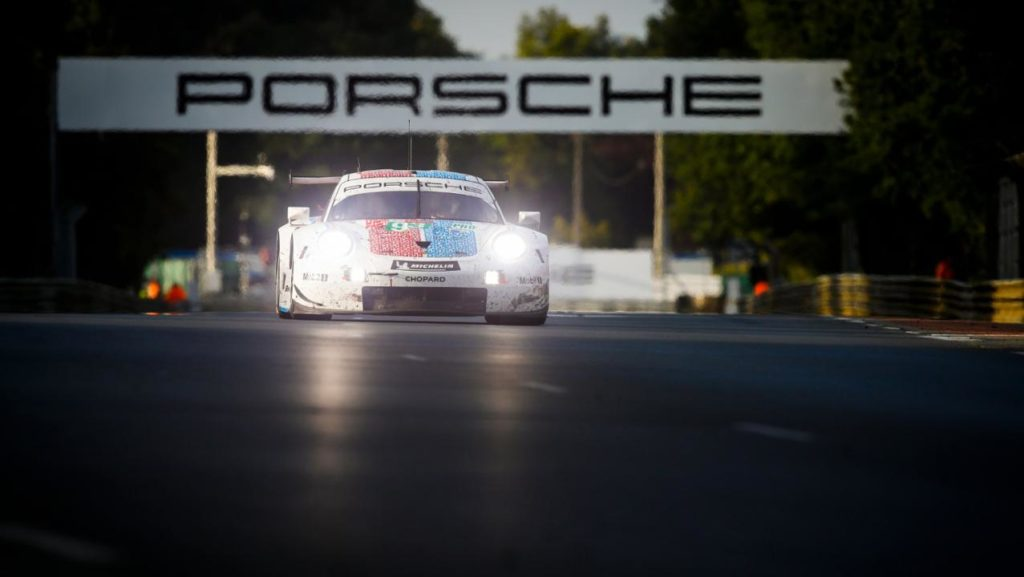 A Porsche 911 RSR tackles the Porsche Curves at dusk in the 2019 Le Mans