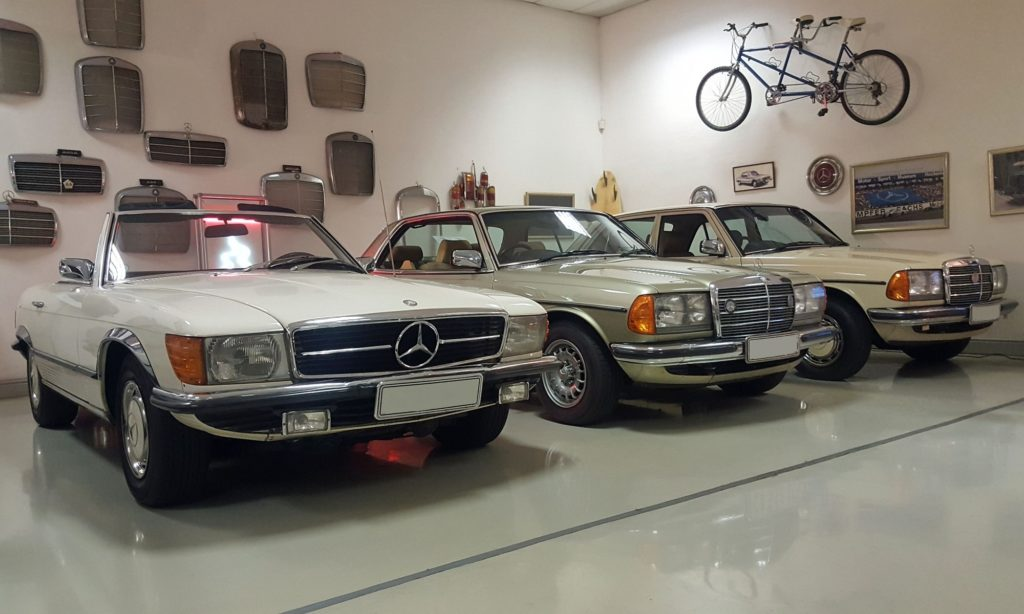 A R107 SL next to a C123 (W123 coupe) variant and W123, on the wall behind are numerous old Mercedes front grilles.