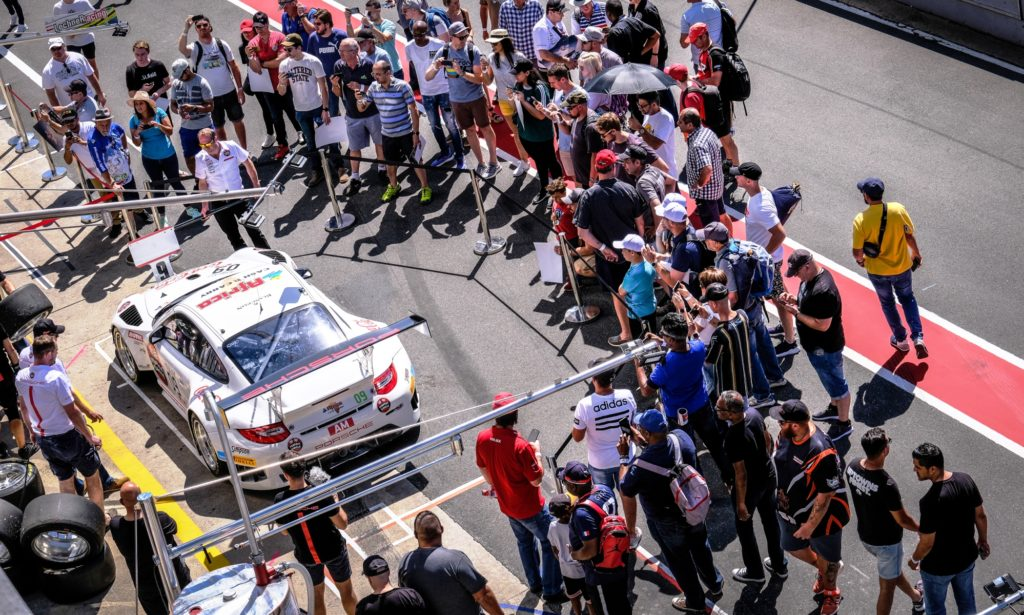 The Team Perfect Circle Porsche surrounded by fans on the Friday pit walk